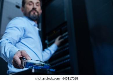 Handsome bearded programmer taking a rack server