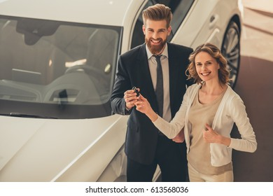 Handsome bearded sales manager is giving a key to beautiful client of car dealership, both are smiling