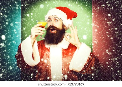 handsome bearded santa claus man with long beard on smiling face holding glass of alcoholic beverage in christmas or xmas sweater and new year hat showing ok on colorful studio background