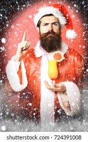 handsome bearded santa claus man with long beard on serious face holding glass of nonalcoholic cocktail in christmas or xmas sweater and new year hat wirh raised finger on red studio background