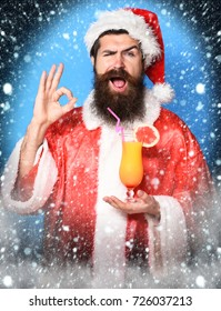 handsome bearded santa claus man with long beard on funny face holding glass of nonalcoholic cocktail in christmas or xmas sweater and new year hat showing ok on blue studio background