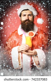 handsome bearded santa claus man with long beard on serious face holding glass of nonalcoholic cocktail in christmas or xmas sweater and new year hat on red studio background