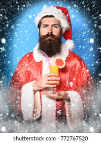handsome bearded santa claus man with long beard on serious face holding glass of nonalcoholic cocktail in red christmas or xmas sweater and new year hat on blue studio background