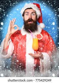 handsome bearded santa claus man with long beard on surprised face holding glass of nonalcoholic cocktail in christmas or xmas sweater and new year hat showing ok on blue studio background