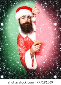 handsome bearded santa claus man with long beard on serious face holding glass of alcoholic beverage in christmas or xmas sweater and new year hat on colorful studio background