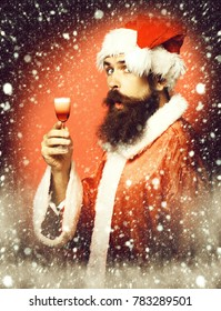 handsome bearded santa claus man with long beard on funny face holding glass of alcoholic shot in christmas or xmas sweater and new year hat on red studio background
