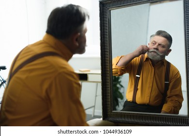 handsome bearded senior man adjusting moustache and looking at mirror