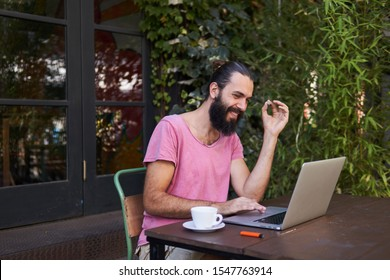 Handsome bearded smiling male using laptop at the cafe terrace and smoking marijuana joint