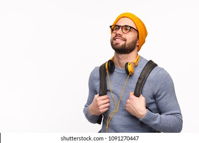 Handsome bearded student wearing glasses with hand and headphones looking up in thinking and smiling on white.