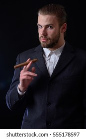 handsome bearded stylish business man in elegant black suit posing in studio with cigar on black background