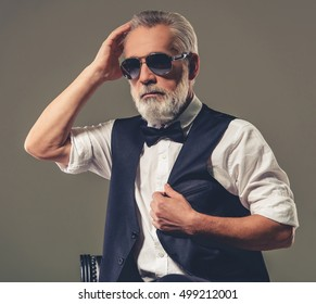 Handsome bearded stylish mature man in shirt, waistcoat, bow tie and glasses is smoothing his hair and looking away, on a gray background