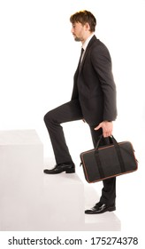 Handsome bearded stylish young businessman climbing stairs with a briefcase in his hand