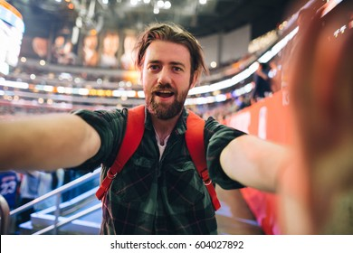 Handsome bearded supporter watching basketball game and making selfie self-portrait with smartphone at stadium