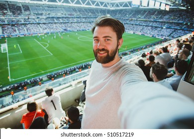 Handsome bearded supporter watching football game and making selfie self-portrait with smartphone at Camp Nou Stadium in Barcelona, Spain