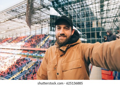 Handsome bearded supporter watching football game and making selfie self-portrait with smartphone at stadium.