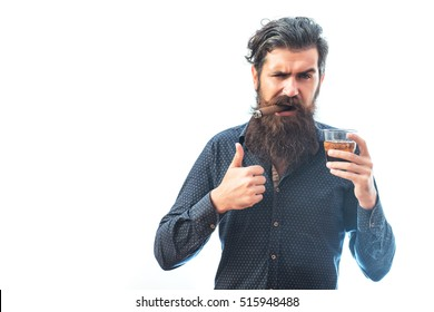 handsome bearded tough rich man with stylish hair mustache and long beard on serious face in blue fashion shirt smoking cigar holding glass of whiskey and showing cool isolated on white, copy space
