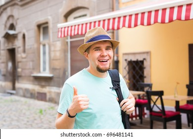 Handsome bearded tourist with backpack is making travel across city. Man standing and giving thumb up.