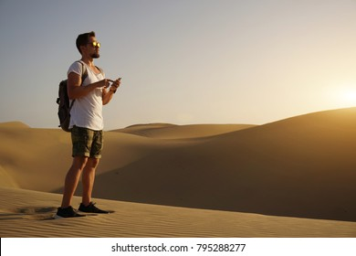 Handsome bearded tourist guy standing with his smartphone in the middle of the desert.