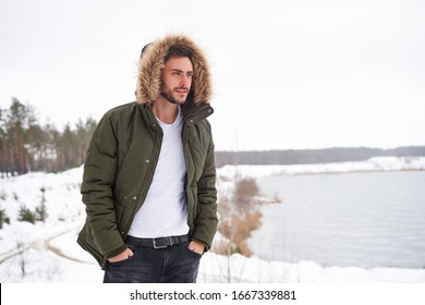 Handsome bearded young caucasian man standing outdoors fur hood in winter season forest. Attractive stylish european guy walking snowy christmas woodland Season holiday leisure