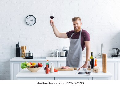 handsome bearded young man in apron holding glass of red wine and smiling at camera while cooking in kitchen