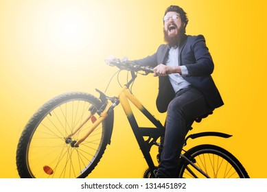 A handsome bearded young man in eyeglasses  and suit riding bicycle on yellow background
