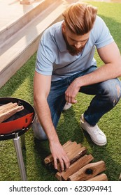 Handsome bearded young man looking at firewood for outdoor grill