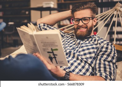 Handsome bearded young man is reading a book and smiling while lying in the hammock in modern library