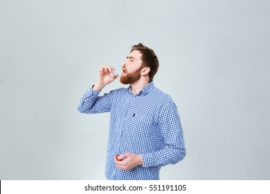 Handsome bearded young man taking pills from the bottle