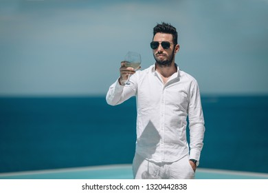 Handsome bearded young man  in white shirt  and black sunglass drinking wine near pool. Summe vacation. Phuket. Thailand.
