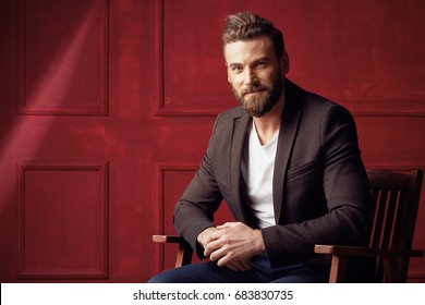 Handsome beautiful bearded man, wearing white shirt and brown jacket, sitting on wooden chair in studio with dark red background