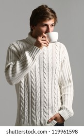 Handsome and beautiful man in white sweater drinking tea