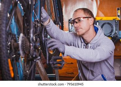 handsome bicycle mechanic doing his professional work in workshop.