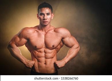 Handsome big muscles man posing at studio.