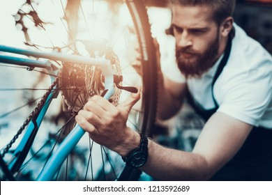 Handsome Bike Mechanic Repairs Bicycle in Workshop. Closeup Portrait of Young Bearded Man Wearing White T-Shirt Fixes Modern Cycle Transmission System. Bike Maintenance and Sport Shop Concept