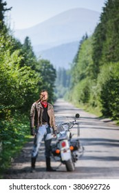 Handsome biker with long hair wearing leather jacket blue jeans leather boots and gloves standing near his custom made cruiser motorcycle on the open road. Looking to the camera. Tilt soft effect