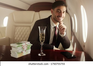 Handsome billionaire in suit and tie sitting next to window in his private jet with glass of champagne and packs of banknotes, smiling happily, satisfied with income