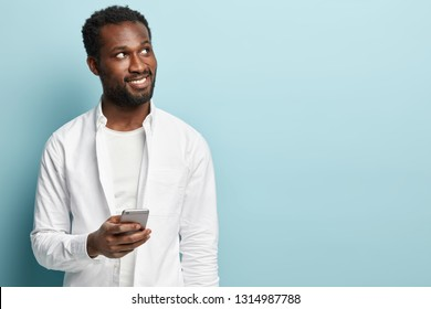 Handsome black adult man with bright smile, dressed in white shirt, carries mobile phone, focused upwards with pleased expression, enjoys online communication, isolated over blue background.