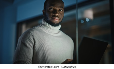 Handsome Black African American Male is Standing in Meeting Room Behind Glass Walls with a Laptop Computer in an Creative Agency. Project Manager Wearing White Jumper and Working in Empty Quiet Room.