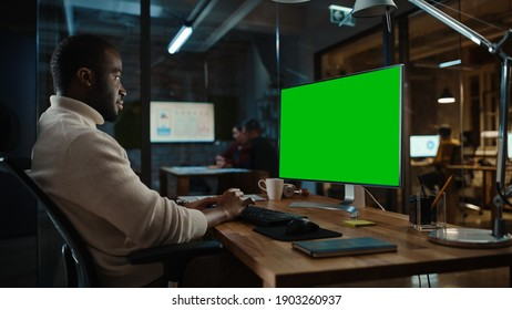 Handsome Black African American Project Manager is Making a Video Call on Desktop Computer with Green Screen Mock Up Display in a Busy Creative Office. Male Specialist is Wearing Turtle Neck Sweater.