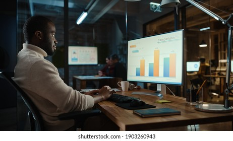 Un bonito afroamericano negro trabajando en computadoras de escritorio en un ambiente de oficina creativa. Persona de color está desarrollando un nuevo diseño de aplicaciones e interfaz de usuario en un software de edición de gráficos digitales.