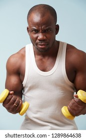 Handsome black bold man in sleeveless white shirt doing biceps curls with light yellow-collored plastic dumbbells. pale blue background. Tensing biceps. Angry irritation on his face. Fitness workout.