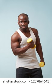 Handsome black bold man in sleeveless white shirt doing biceps curls with light yellow-collored plastic dumbbells. pale blue background. Tensing biceps. Serious manly face expression. Fitness workout.