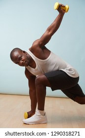 Handsome black bold man in sleeveless white shirt doing waist rotations with two light yellow-collored plastic dumbbells. pale blue background. Fitness workout. Touching floor. Stretching.