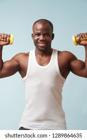 Handsome black bold smiling man in sleeveless white shirt lifting up two light yellow-collored plastic dumbbells. pale blue background. Tensing biceps. Fitness workout.