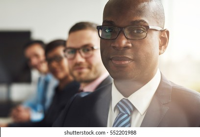 Handsome black business man with three employees and back to large bright office window with light flare