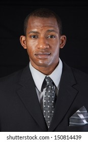 Handsome black businessman ina suit and tie, looking at the camera with a focused, serious expression,