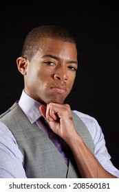 Handsome black businessman in shirt, tie and vest, and looking thoughtful