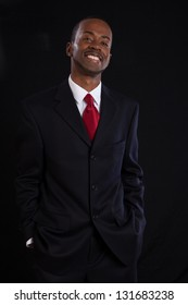 Handsome black businessman smiling with joy, his hands in his suit pants pockets