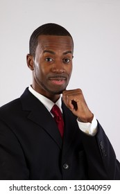 Handsome black businessman in suit and red tie with a white shirt looking thoughtful with his chin on his hand