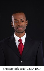 Handsome black businessman in suit and red tie with a white shirt looking at the camera with a confidant smile